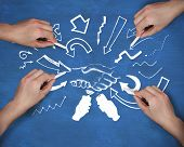Composite image of multiple hands drawing handshake with chalk against navy blue