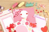 Beautiful hand made post cards and scrapbooking elements, on wooden table