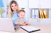 Pretty woman with baby working at home