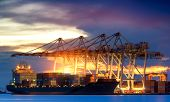 stock photo of shipyard  - Container Cargo freight ship with working crane bridge in shipyard at dusk for Logistic Import Export background - JPG