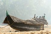 Fishing Boat On The Beach Against Jungle Background