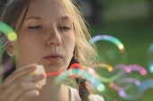 Teenage Girl Blows Soap Babbles In Te Park
