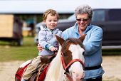 image of carnival ride  - A happy boy rides a pony for the first time with his grandmother supporting him by his side - JPG