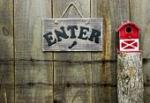 Enter sign over barbed wire fence post with red barn birdhouse