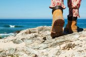 Closeup Hiking boots  on mountain rocks with sea in background. Focus on sole