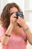 Mature woman taking pictures with old analog SLR camera at home