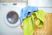image of washing-machine  - Dirty clothes basket with towels waiting for laundry with washing machine in backround - JPG