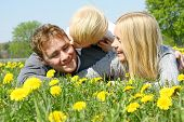 Child Kissing Father And Mother In Flower Meadow