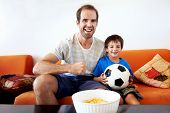 Father and son watching football world cup soccer on tv together in living room on sofa being excite