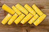 stock photo of zea  - Fresh yellow corn on the cob arranged in a pointer on a rustic wooden table at farmers market overhead view - JPG