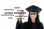 picture of verbs  - Female student in gown writes english language materials on whiteboard - JPG
