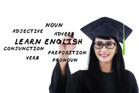 stock photo of verbs  - Female student in gown writes english language materials on whiteboard - JPG