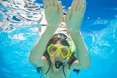 Woman wears snorkeling mask swimming underwater