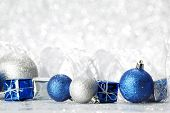 Decorative Christmas balls and gifts on silver bokeh background