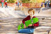 Happy blond boy with green skateboard sitting