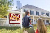Curious Family Facing Sold For Sale Real Estate Sign and Beautiful New House.