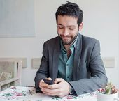 Young man wearing jacket sitting in restaurant and typing  on phone.