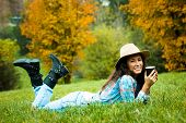 smiling young woman enjoy in coffee break in nature, lie on grass in park, wearing hat and blue jeans and  tartan shirt, full body shot, look at camera