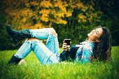 smiling young woman enjoy in coffee break in nature, lie on grass in park, wearing blue torn jeans and tartan shirt, full body shot