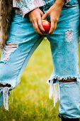 close up of a woman hands hold an apple, wearing blue torn jeans, fur vest and tartan shirt
