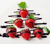 Strawberries  In Chocolate Sauce On A  White Plate.