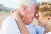 stock photo of elderly couple  - a happy senior couple kissing on the beach outdoors - JPG