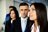 Group of young co-workers standing in a row at office