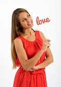 picture of sweethearts  - Pretty young woman in a red dress standing holding a the word  - JPG