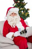 Santa shopping online on the couch on white background