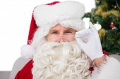 Perplexed santa claus holding his glasses on white background