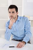 Handsome young manager sitting in the office thinking about sense of life.