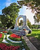 Elegant marble arch frames the bronze statue of Johann Strauss. Wonderful park in the center of Vienna
