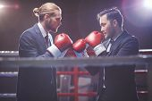 Businessmen in suits and boxing gloves fighting on boxing rink
