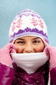 Face of charming girl in warm winterwear looking at camera