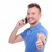 picture of a young casual man talking on the phone while showing the thumb up gesture with a smile on his face. isolated on a white background