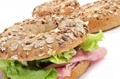 a brown bagel topped with different seeds, such as sesame and poppy seeds, filled with ham and lettuce mix on a white background