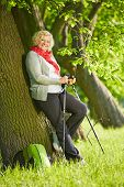Happy senior woman with hiking sticks leaning on a tree