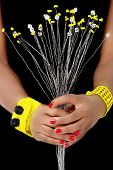 Hands of an African Woman hold White and Yellow Beaded Flowers, with Yellow and Black Bracelets, on