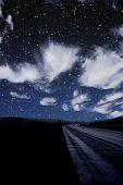 Single car travels on dark road under stars