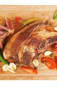 fresh roasted lamb meat fillet ready on wooden board with tomatoes and red pepper isolated  over white background