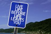 Live Life Before Life Leaves You sign with a beach on background