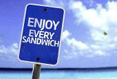 Enjoy Every Sandwich sign with a beach on background