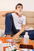 image of teen smoking  - Sick Teenager smoking Cigarette on the Sofa with the Pills on foreground - JPG