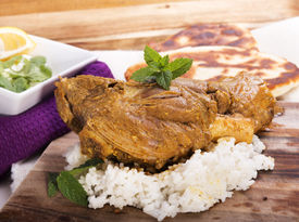 foto of lamb shanks  - Slow cooked lamb shanks served on wooden board with rice and gluten free naan bread  - JPG