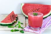 picture of mints  - Glass of fresh watermelon juice with mint leaves and sliced fruit on wooden table - JPG