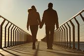 picture of bridge  - Back silhouette of a couple walking holding hands on a bridge in the beach at sunset - JPG