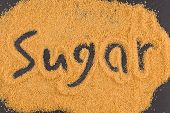 stock photo of sugar  - word sugar written in brown granulated sugar on dark stone background - JPG