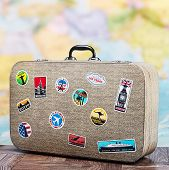 image of cartographer  - retro suitcase with stikkers on the floor against the backdrop of a world map - JPG