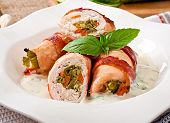 stock photo of bacon strips  - Delicious chicken rolls stuffed with green beans and carrots wrapped in strips of bacon with yoghurt and basil sauce - JPG