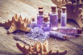 stock photo of gels  - Bottles with shower gel sea salt and starfish on wooden background - JPG